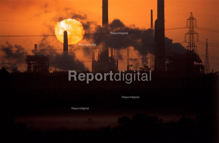 Sunrise over the chimneys of a refinery plant. - Paul Carter - 1996-11-03