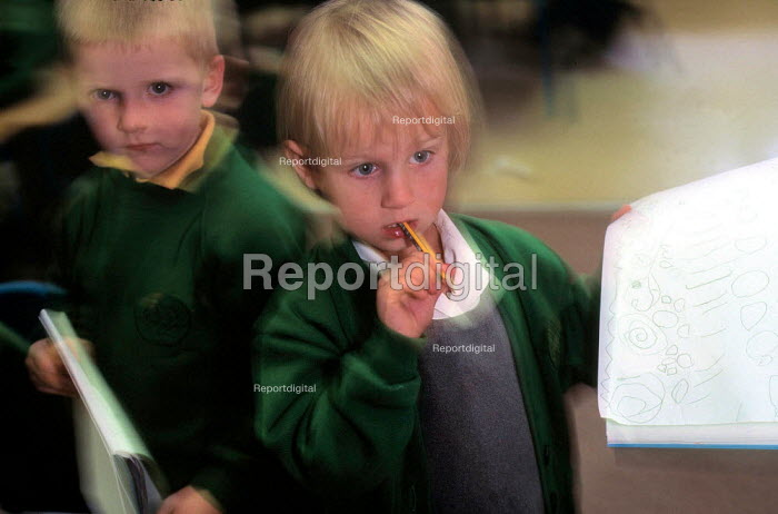 Two young school children holding pads of paper with drawings on. - Paul Carter - 1999-10-20