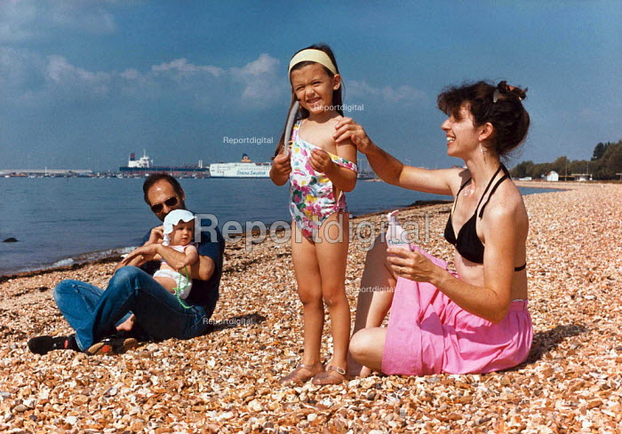 Mother applying sunscreen to her young daughter's shoulder with father holding the baby in the background. - Paul Carter - 1993-08-30