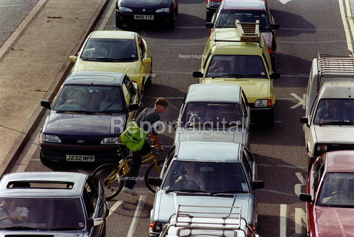 Cyclist weaving between cars queuing at a busy road junction. - Paul Carter - 1995-09-08