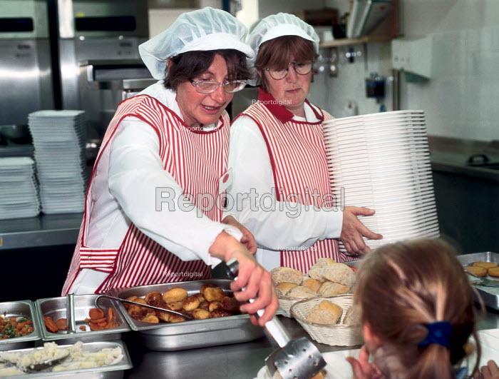 Two dinner ladies serving food to school children. - Paul Carter - 1997-05-07