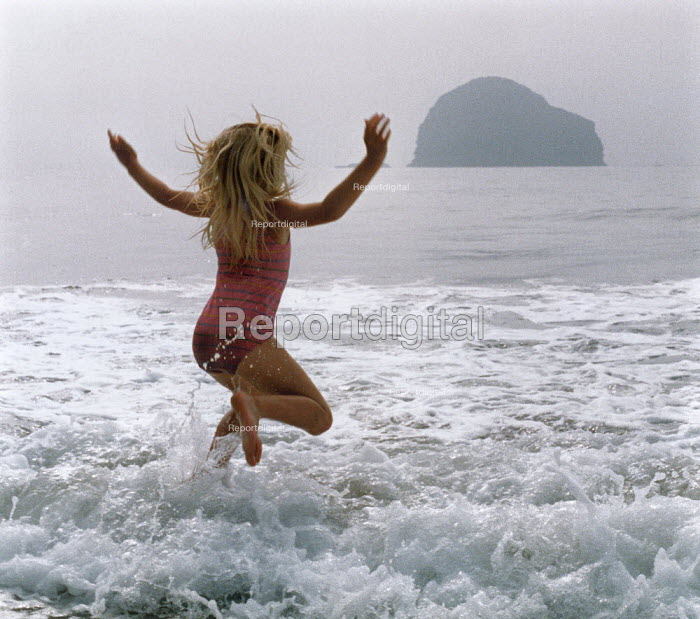 Young girl jumping in the waves on a beach. - Paul Carter - 1988-08-01