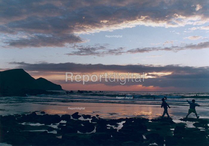 Childen playing on a beach at sunset. - Paul Carter - 1990-08-01