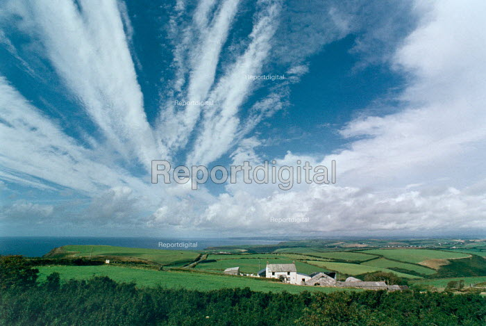 Coastal farmstead with dramatic cloud formation in the sky. - Paul Carter - 1990-08-01