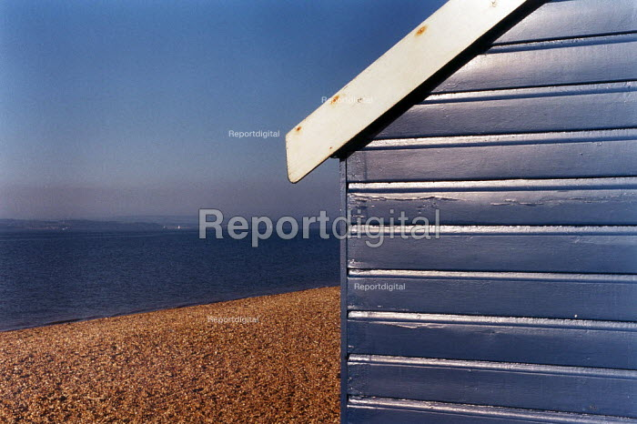 Looking past a brightly painted beach hut, to a stoney beach, sea and The Isle of Wight. - Paul Carter - 1994-05-31