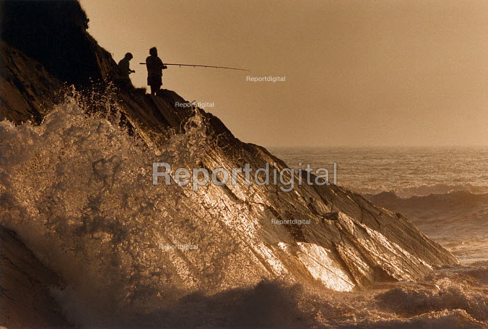 Man and boy fishing in the sea from the edge of a cliff. Waves are crashing on the rocks below. North Cornwall. - Paul Carter - 1993-08-01
