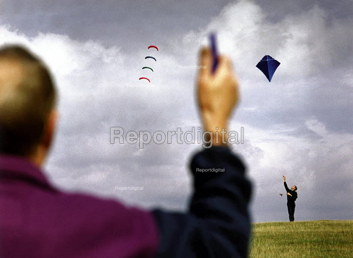 Two people flying kites on a hilltop. - Paul Carter - 1995-10-01