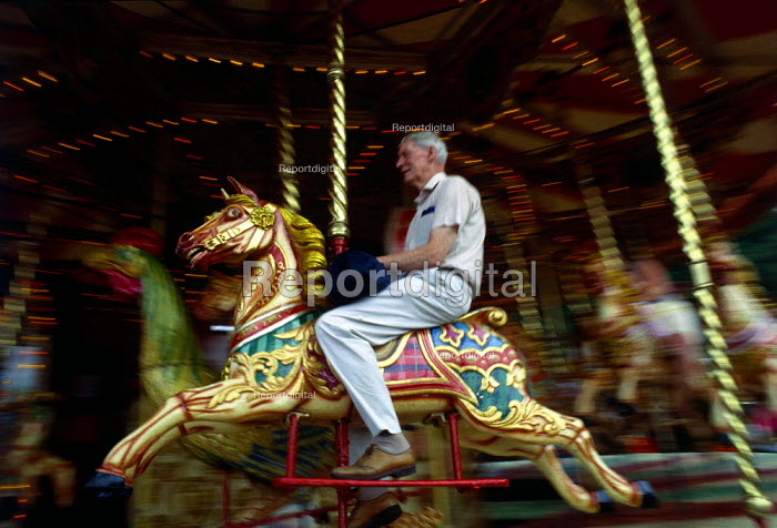Man rides on a merry-go-round horse. - Paul Carter - 1989-07-20