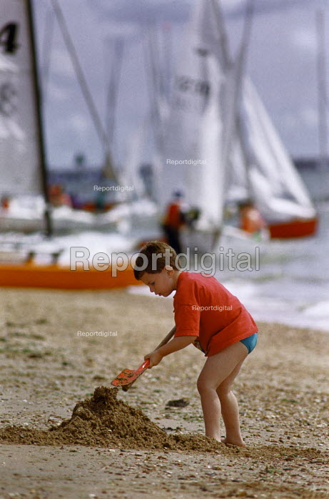 Young boy digging on a sandy beach. Yachts rigged up in the background. - Paul Carter - 1993-08-01