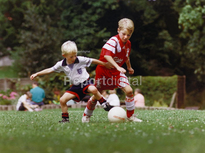 Two young boys playing football in a park. - Paul Carter - 1993-08-01