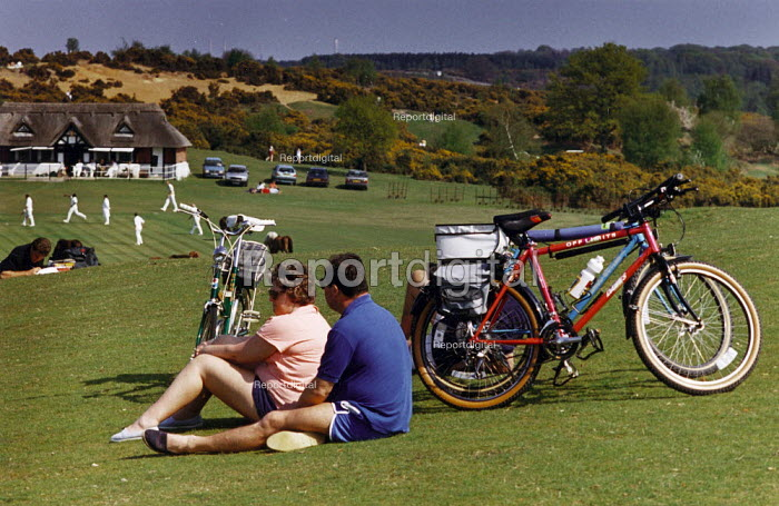 Couple resting with bicycles propped up beside them. Cricket match being played in the distance. - Paul Carter - 1994-05-03