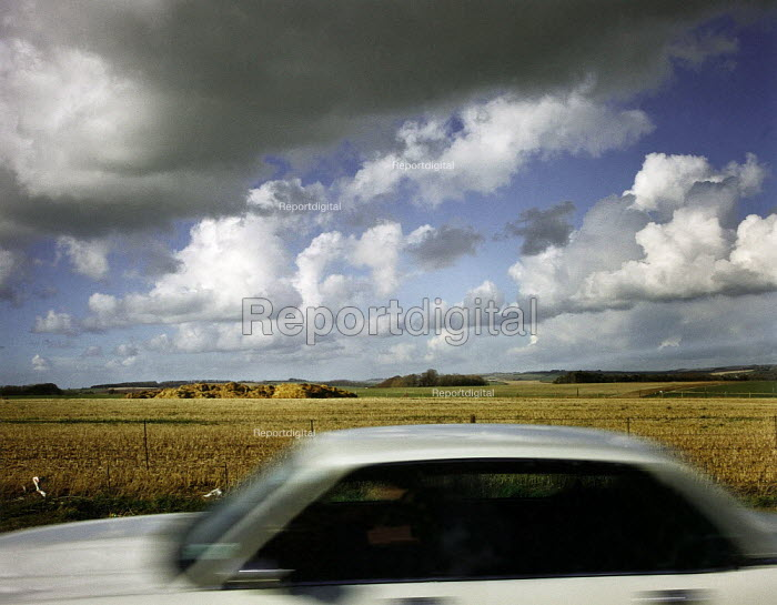 Car driving through the countryside, under a cloudy sky. - Paul Carter - 1995-03-17