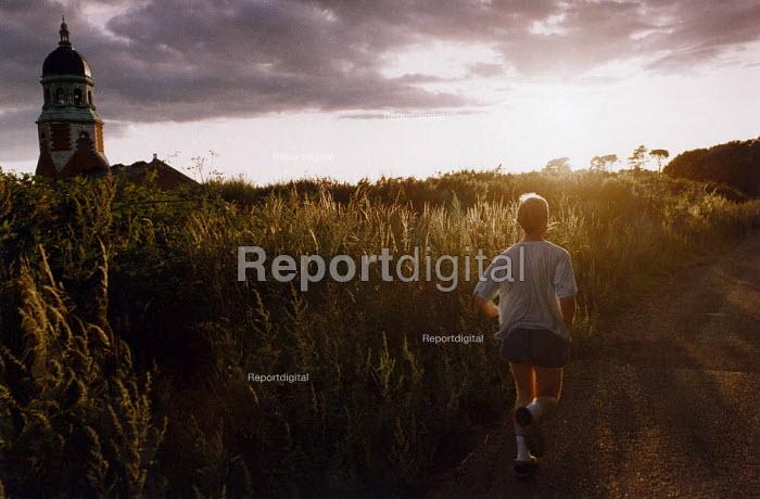 Jogger running past tall grass, at sunset. - Paul Carter - 1993-08-01