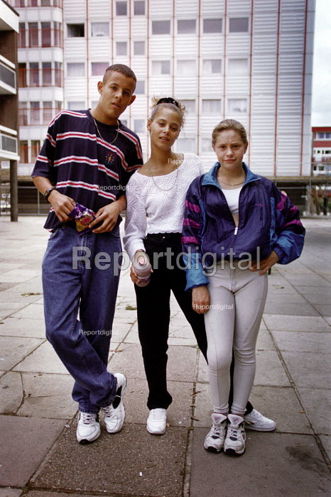 Three young friends in front of a high rise block of flats on an estate. - Paul Carter - 1995-08-28