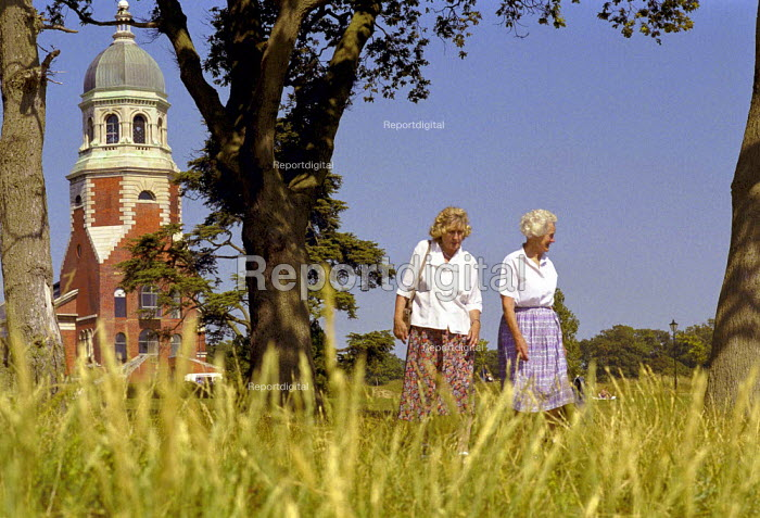 Two women enjoying a summer walk through the grounds of Royal Victoria Country Park, with the red brick chapel in the background. - Paul Carter - 1996-07-20