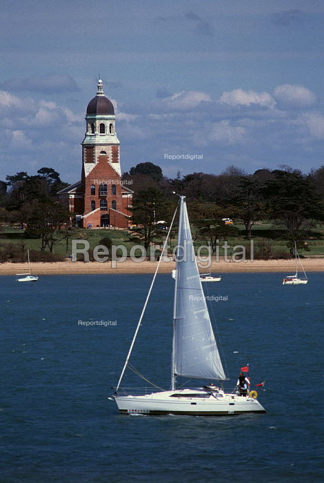 Yacht sailing past the Chapel (now a museum) in Royal Victoria Country Park. - Paul Carter - 1989-04-15