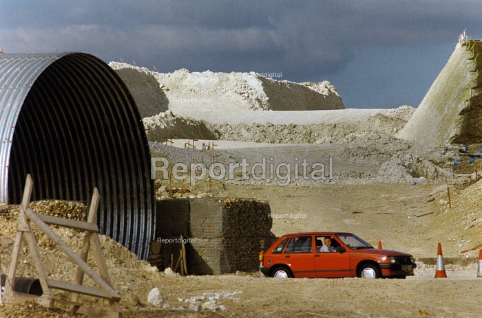 Car driving through roadworks during the construction of the M3 motorway by-pass. - Paul Carter - 1993-08-06
