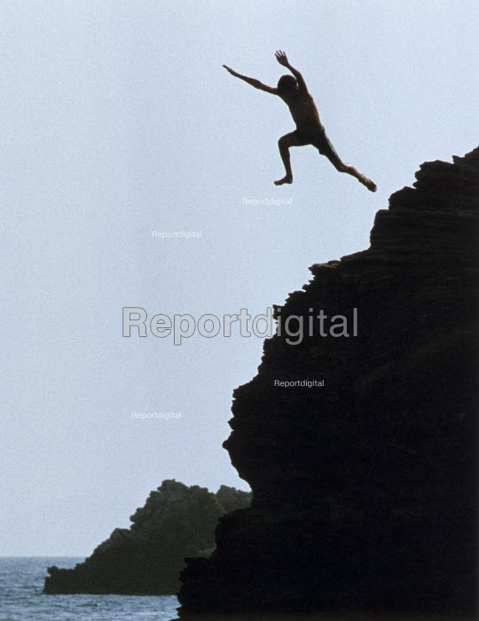 Youth leaping from rocks into the sea. - Paul Carter - 1991-08-01