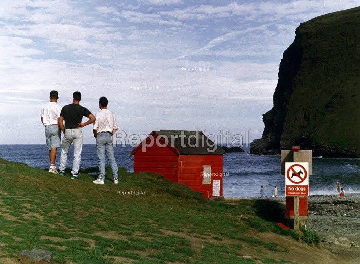 Three friends looking out to sea. - Paul Carter - 1990-08-01