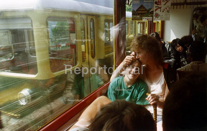 Mother and son sitting on a busy train, looking out of the window, Switzerland - Paul Carter - 1991-08-18
