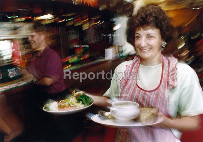 Woman serving food in a pub. - Paul Carter - 1993-09-05