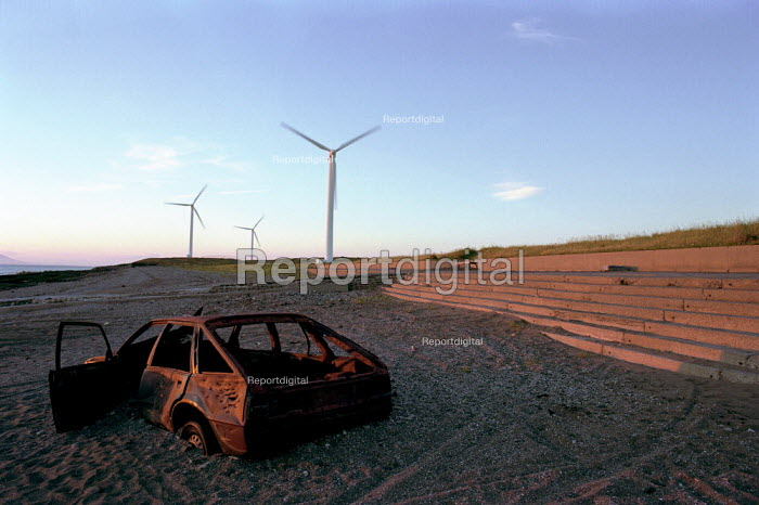 Burnt out car on a shngle beach, with energy producing windmills in the background. Taken at sunset. Cumbria. Winscales Moor Wind Farm - Paul Carter - 2000-07-17