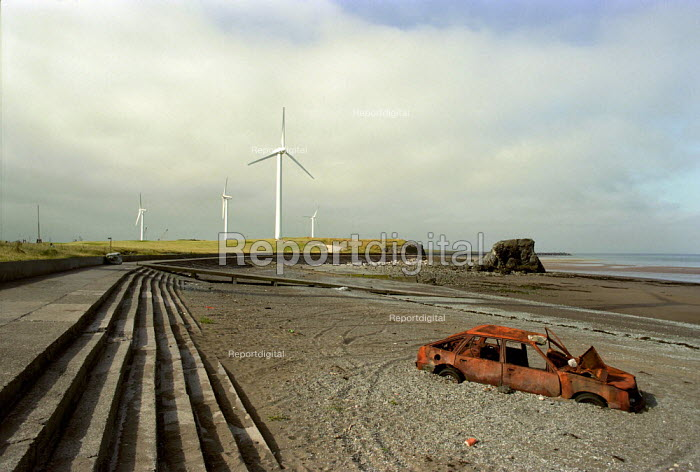 Burnt out car abandoned on a shingle beach in Cumbria. Windfarm windmills in the background.  This wind farm generates enough power for 5,700 homes, saving 24,560 tonnes of Greenhouse gases a year. - Paul Carter - 2000-07-17
