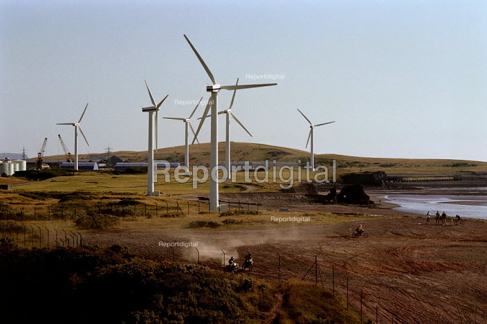 Wind turbines on the coast in Cumbria. Youths are riding motorbikes. This wind farm generates enough power for 5,700 homes, saving 9,350 tonnes of CO2 emissions a year. - Paul Carter - 2000-07-17