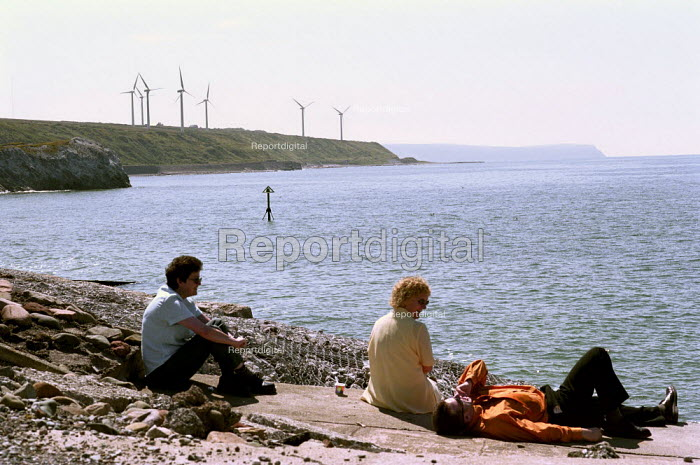 Workers relaxing during their lunch break on the coast of Cumbria.  This windfarm supplies 3,800 homes and saves 15,225 tonnes of green house gasses a year. - Paul Carter - 2000-07-17