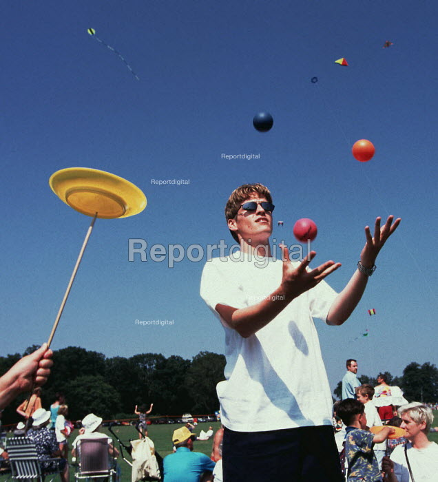 Young man juggling. Kites flying in the background. - Paul Carter - 1996-08-18