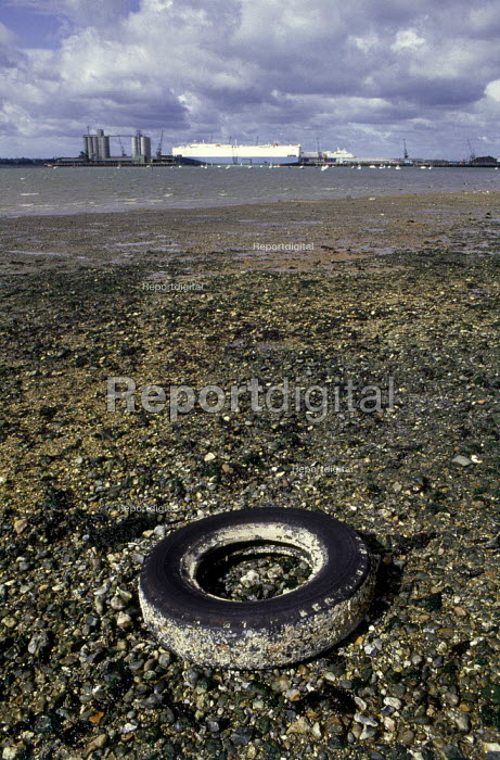 An old car tyre littering the beach. In the background there is a docked ship. - Paul Carter - 1991-04-01