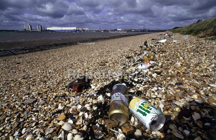 Litter washed up on a stony beach. In the background there is a ship in the docks. - Paul Carter - 1991-04-01