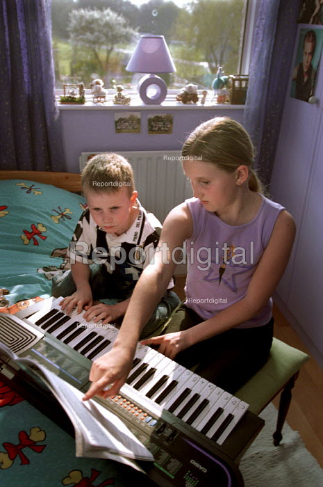 Two children practicing playing their electronic keyboard after school. - Paul Carter - 2002-04-04