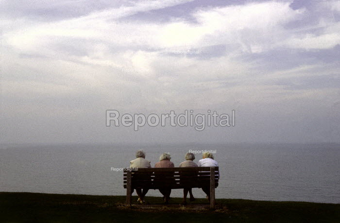 Four elderly women sitting on a bench, looking out to sea. - Paul Carter - 2001-09-17