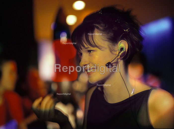 Young woman in a nightclub, talking on a mobile phone - using a hands free kit. - Paul Carter - 2000-02-10