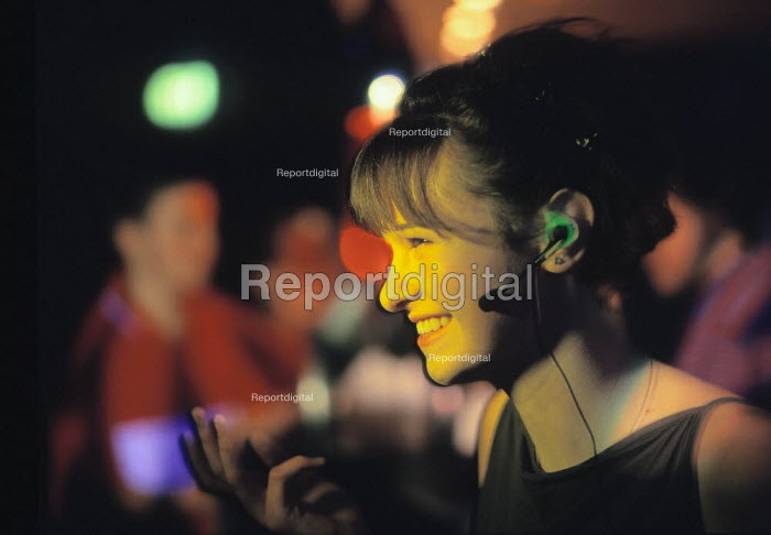 Young woman in a nightclub talking on a mobile phone - using a hands free kit - Paul Carter - 2000-02-10