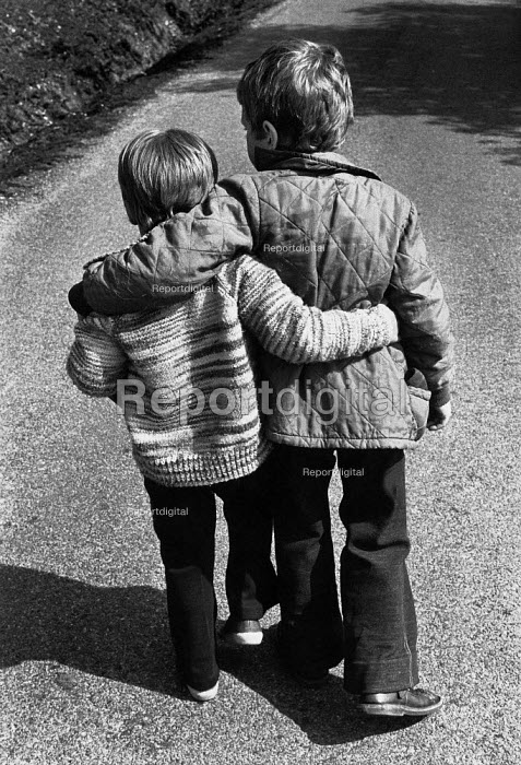 Two boys walking with their arms round each other. - Paul Carter - 1978-09-18