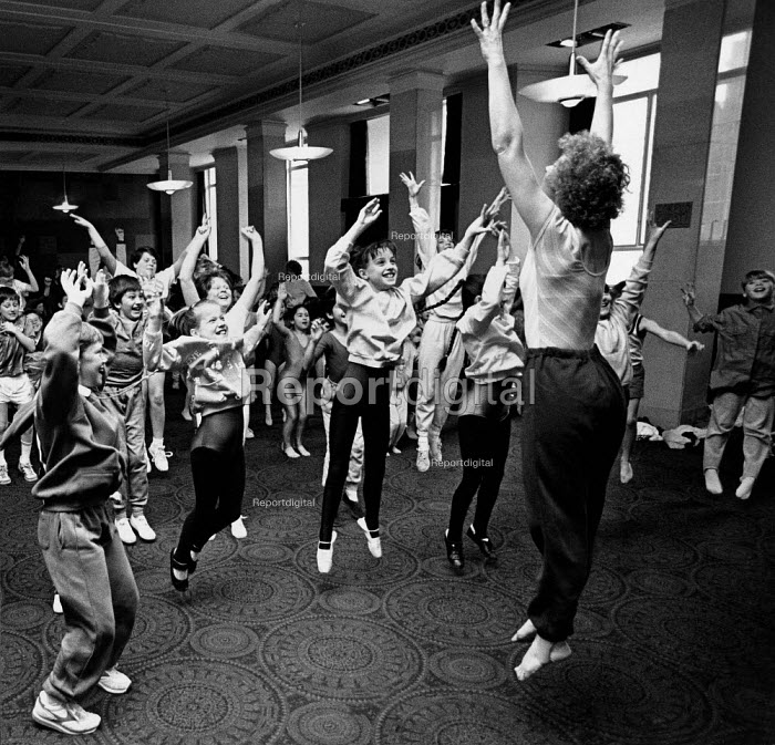 Group of children jumping during a dance lesson, with their teacher. - Paul Carter - 1999-05-18