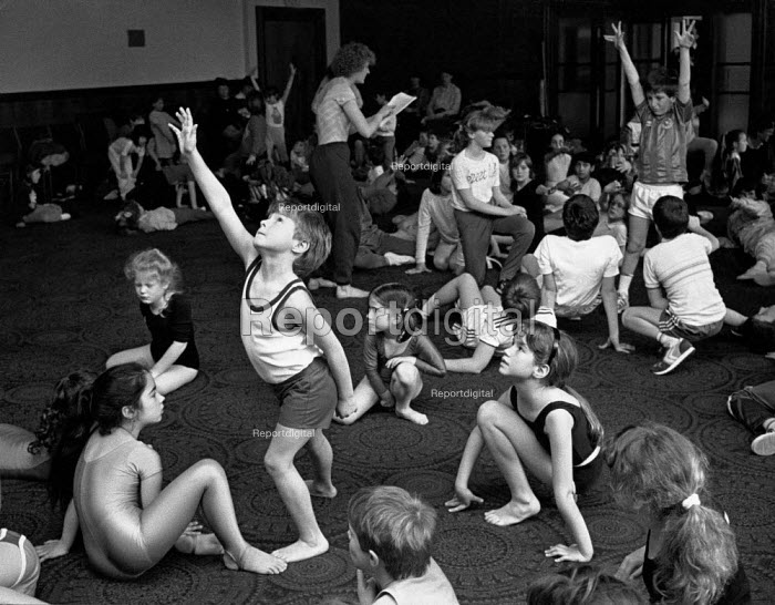 Group of children in a hall, sitting small circles with one child in the middle, reaching up. - Paul Carter - 1999-09-18