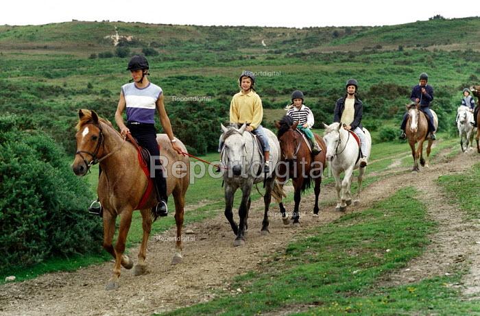 Pony trekkers riding across heathland. - Paul Carter - 1988-08-01