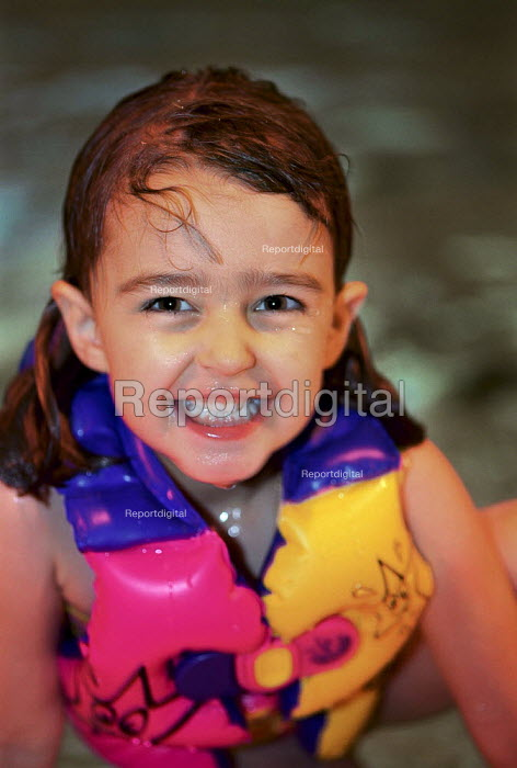 Young girl, wearing a buoyancy vest in the swimming pool. - Paul Carter - 2002-08-11