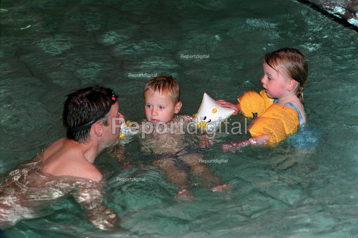 Two young children, playing in the learner pool with their father. - Paul Carter - 2002-08-11