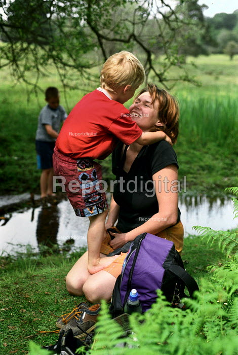 A mother helps her son put his socks on after paddling in a stream, The New Forest, Hampshire - Paul Carter - 2002-06-01