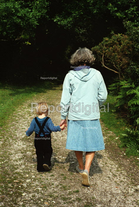 Grandaughter and grandmother walking along a forest path holding hands, The New Forest. - Paul Carter - 1980-04-04