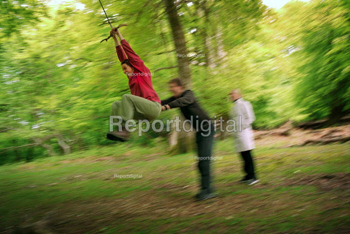Three friends playing on a rope swing in The New Forest. - Paul Carter - 2002-05-20