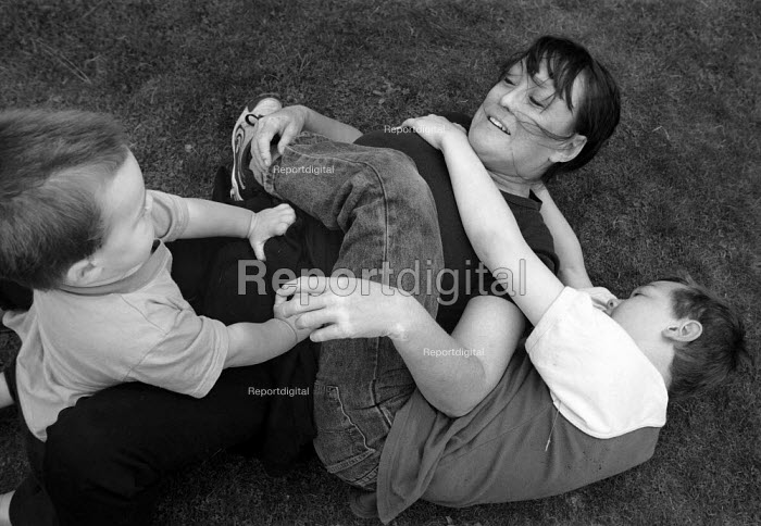 Mother and sons play fighting. - Paul Carter - 2001-09-13