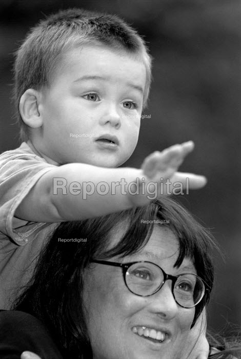 Young boy sitting on his mother's shoulders. - Paul Carter - 2001-09-13
