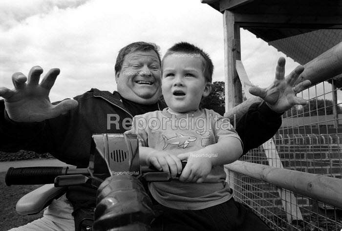 Young boy on his father's lap who is sitting in a motorised scooter, during a day out at the zoo. - Paul Carter - 2001-09-13