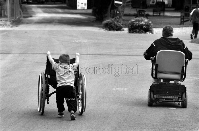 Family during a day out at a zoo. The father is using a motorised chair while his son pushes his wheelchair. - Paul Carter - 2001-09-13