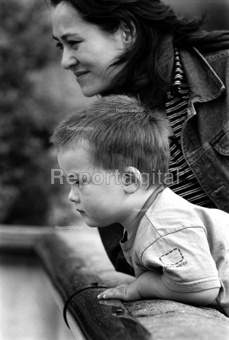 Young boy is loking over the edge of an enclosure at a zoo. - Paul Carter - 2001-09-13